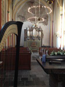 Bruiloftsharpiste Nanja Bakker speelt tijdens trouwceremonie in de Cellebroederkapel in Maastricht